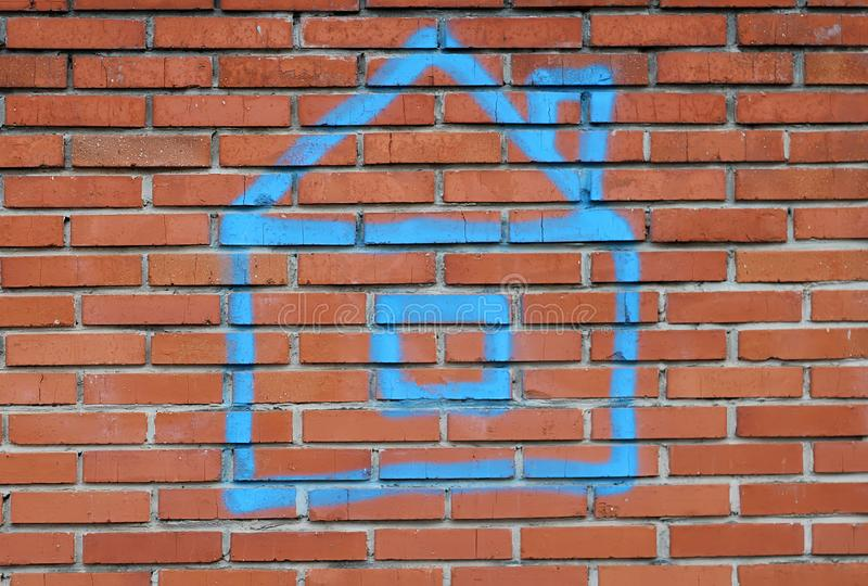 House painted with blue paint on a red brick wall. Real estate concept royalty free stock photography