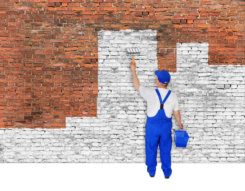 House painter covers brick wall with white paint. House painter covers old brick wall with white paint stock photography
