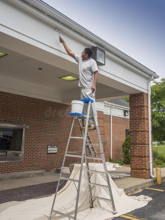 House painter. Finishing off the soffit on a commercial building royalty free stock photography