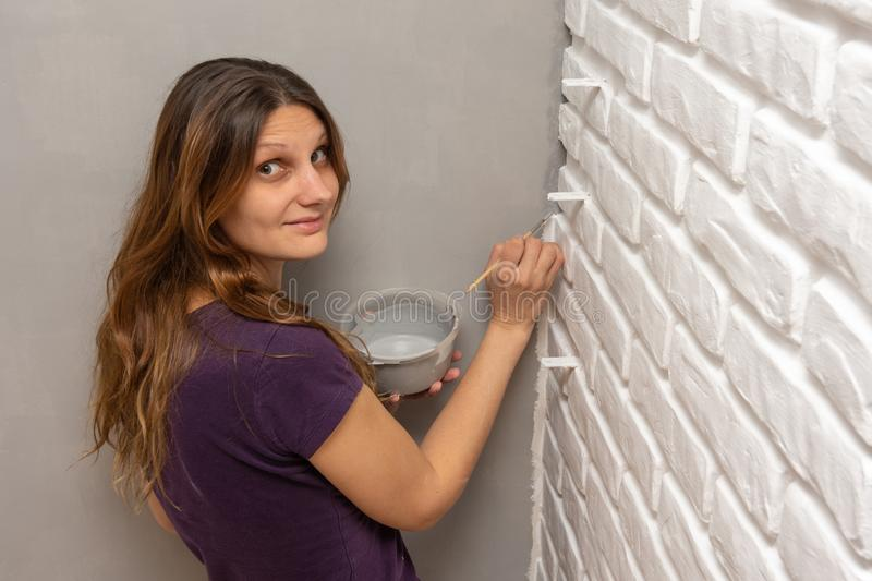 A house painter paints a gray corner of the wall with a small tassel stock photos