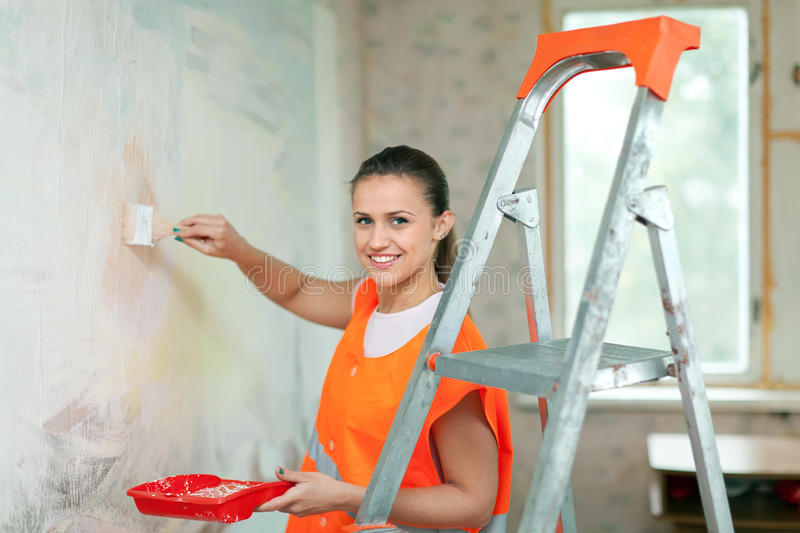 House painter paints wall. Female house painter paints wall with brush stock photos