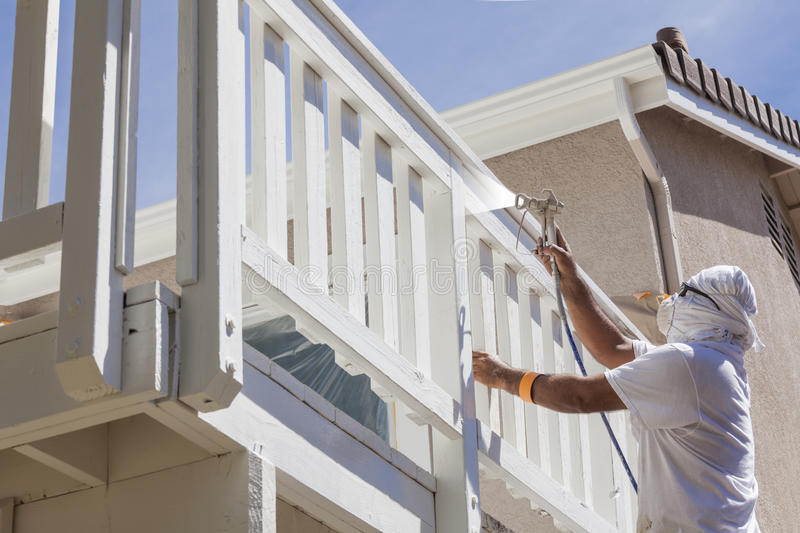 House Painter Spray Painting A Deck of A Home. House Painter Wearing Facial Protection Spray Painting A Deck of A Home stock photography