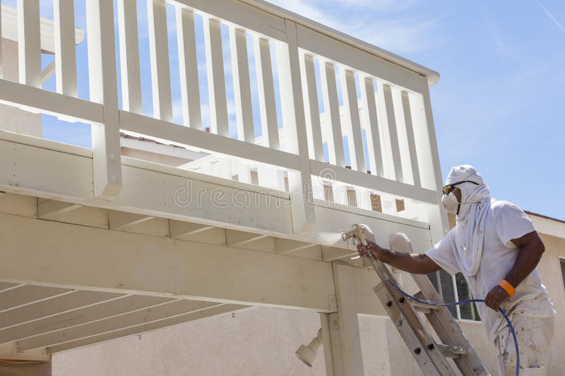 House Painter Spray Painting A Deck of A Home. House Painter Wearing Facial Protection Spray Painting A Deck of A Home royalty free stock photo