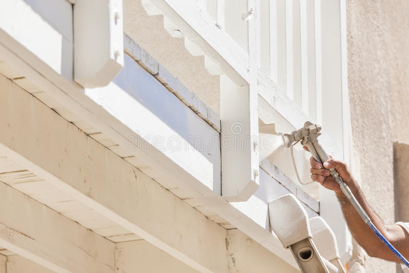House Painter Spray Painting A Deck of A Home. House Painter Wearing Facial Protection Spray Painting A Deck of A Home stock photos