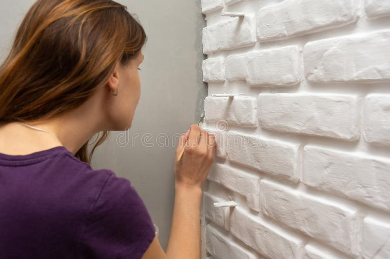 A house painter tends to paint a gray corner of the wall with a small tassel. A house painter tends to paint a gray corner of the wall with a small  tassel stock photo