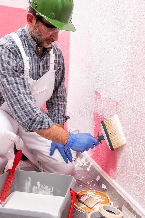 House painter worker at work in the construction site. Building. Caucasian house painter worker in white overalls, with helmet and goggles painting the pink wall royalty free stock image