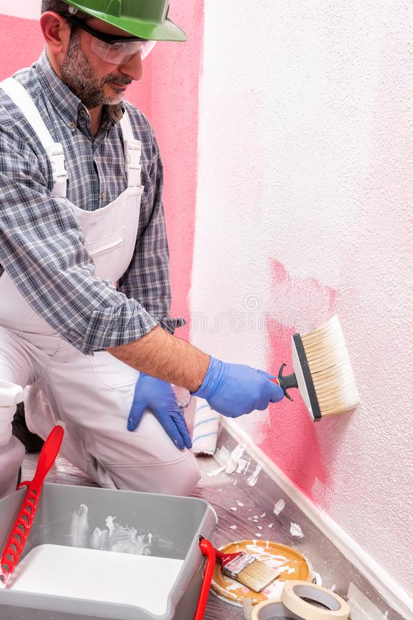 House painter worker at work in the construction site. Building. Caucasian house painter worker in white overalls, with helmet and goggles painting the pink wall royalty free stock photography
