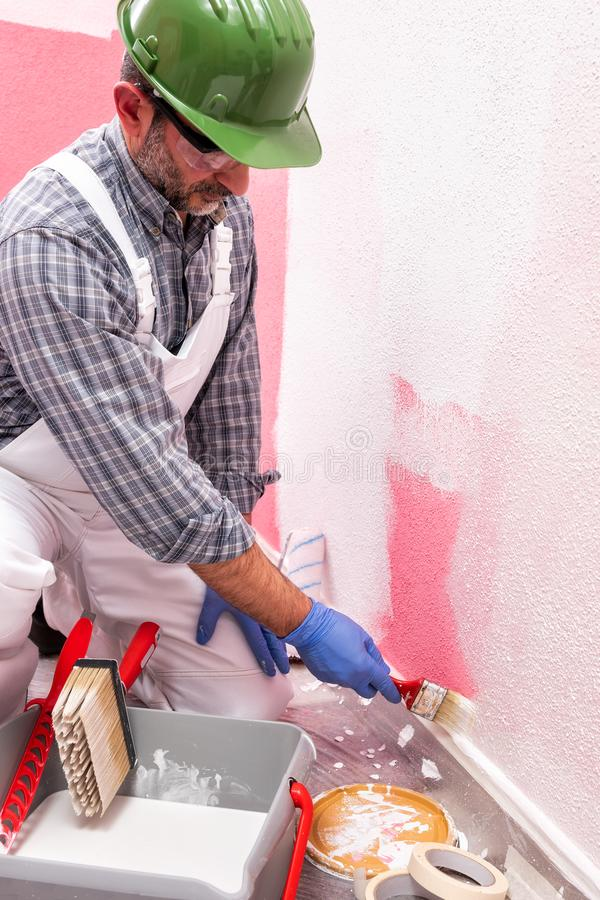House painter worker at work in the construction site. Building. Caucasian house painter worker in white overalls, with helmet and goggles painting the pink wall stock images