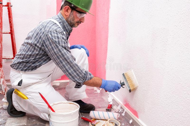 House painter worker at work in the construction site. Building. Caucasian house painter worker in white overalls, with helmet and goggles painting the pink wall royalty free stock images