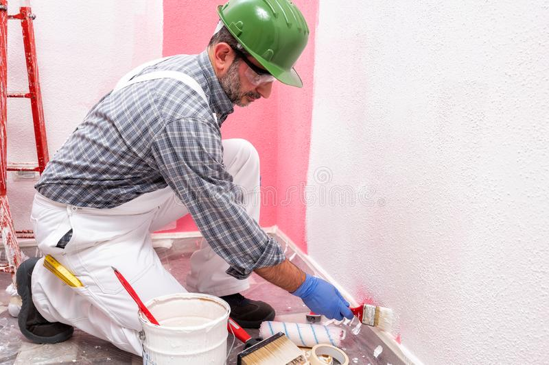 House painter worker at work in the construction site. Building. Caucasian house painter worker in white overalls, with helmet and goggles painting the pink wall stock photos