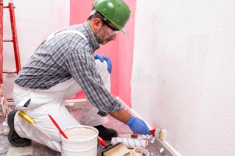House painter worker at work in the construction site. Building. Caucasian house painter worker in white overalls, with helmet and goggles painting the pink wall stock photography