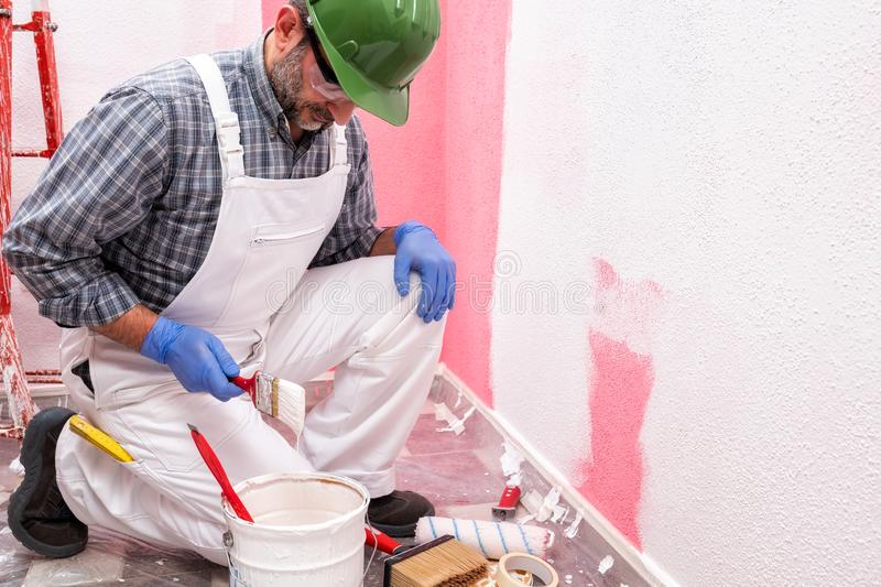 House painter worker at work in the construction site. Building. Caucasian house painter worker in white overalls, with helmet and goggles he prepares the white royalty free stock images