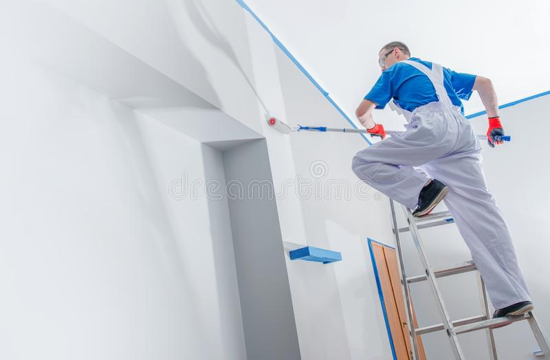 House Painting Business. House Painting and Renovation Business Concept. Caucasian Male Painting House Room From the Ladder royalty free stock images