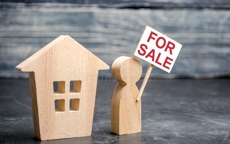House and person with a sign for sale. Sale of real estate by the owner. Attracting customer attention. Mediation and assistance royalty free stock image