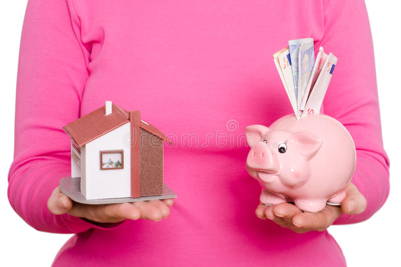 House and piggy bank in a hand. House and pink piggy bank in a female hands stock photo