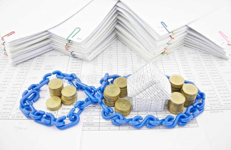House and pile of gold coins in blue plastic chain. On finance account with pile of paperwork as background royalty free stock photo