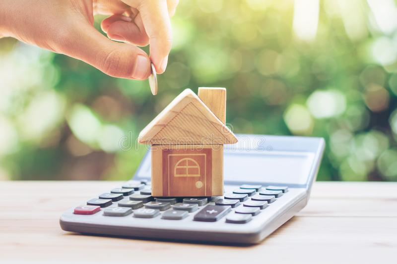 House is placed on the calculator. hand that is coin down the house. planning savings money of coins to buy a home royalty free stock photo
