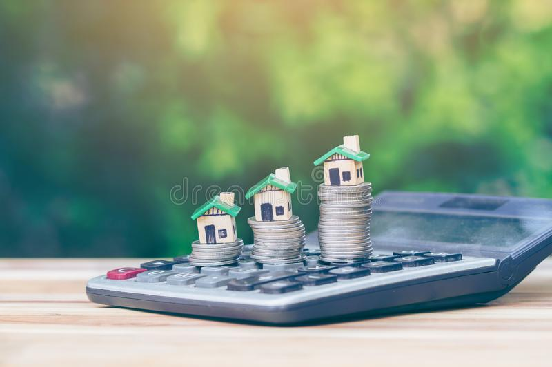 House is placed on a coin as a ladder, is on the calculator. Planning savings money of coins to buy a home concept for property ladder, mortgage and real royalty free stock images
