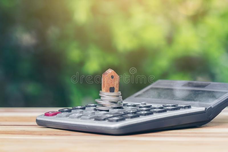 House is placed on the coin is on the calculator. planning savings money of coins to buy a home. Concept, concept for property ladder, mortgage and real estate stock photos