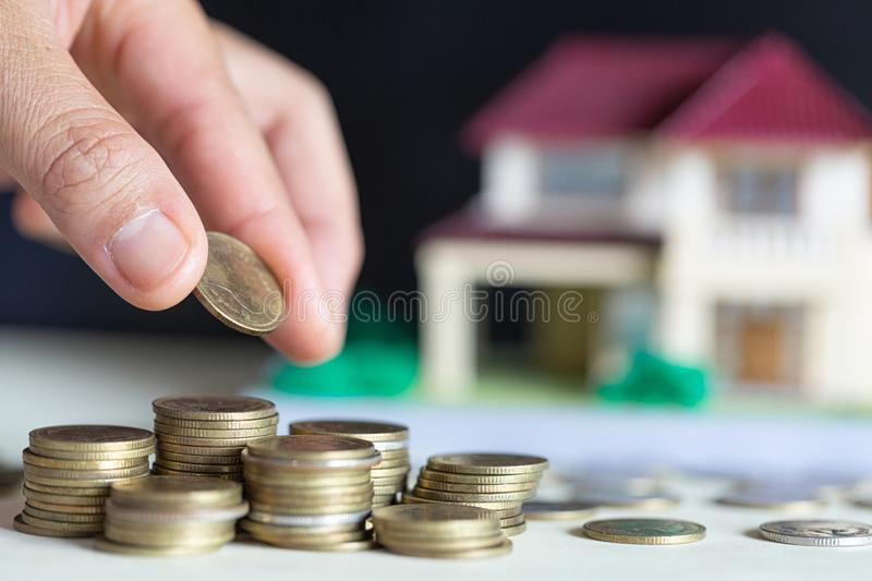 House placed on coins female hand is planning savings money of coins to buy a home stock photo