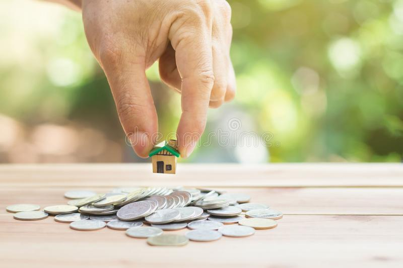 House placed on coins Men`s hand is planning savings money of coins to buy a home stock photography