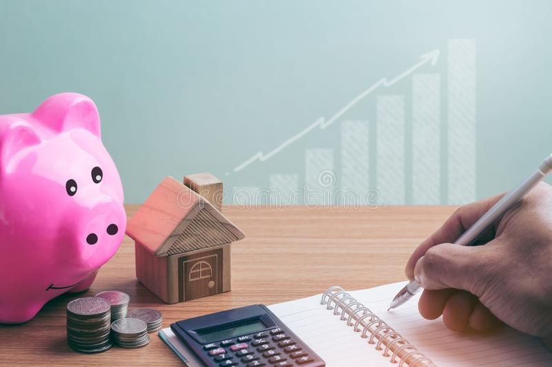 House placed on coins and piggy bank Men`s hand is planning savings money stock photography