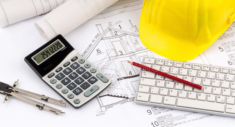House plan with a construction worker's helmet. A blueprint of an architect with the hard hat of a construction worker. symbolic photo for financing and planning stock photo