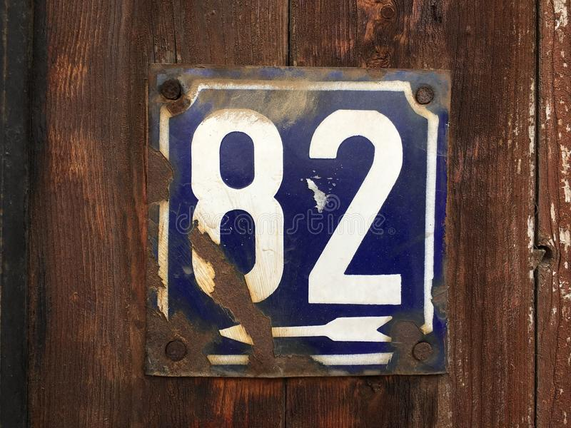 82 on house plate. Metal house number plate with 82 on wooden boards stock images