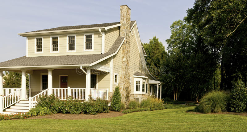 House and porch wide angle. Wide angle of a modest suburban house with a large white porch, green front lawn, flowers and landscaping stock photos