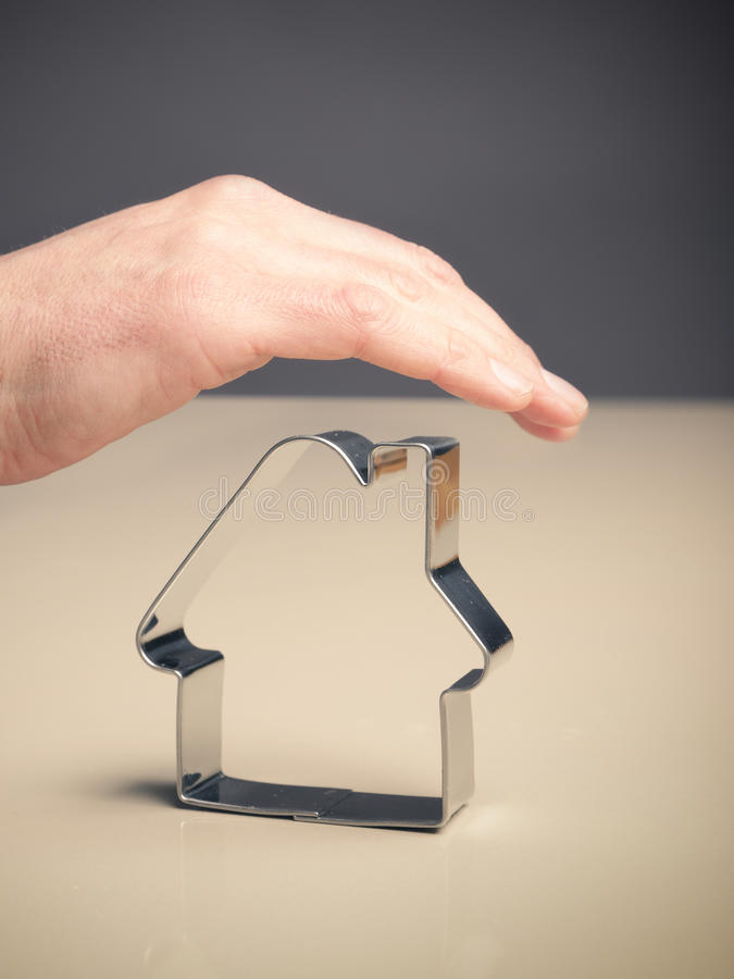 House protection, safety concept. Hand protecting a house shape, safety concept image royalty free stock images