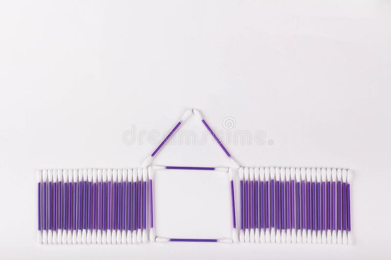 House of purple cotton buds on a white background, copy space. House of purple cotton buds on a white background, hygiene concept, copy space ear plastic swab stock photos