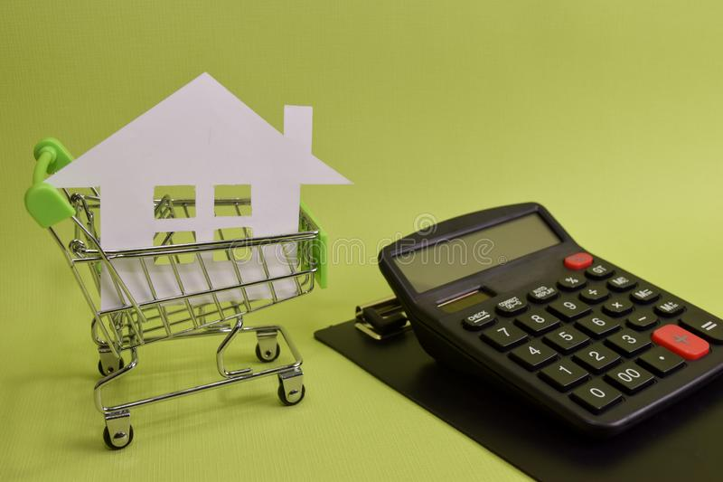 House put in a shopping cart and calculator on the desk. Savings for home, buying houses, sell houses, real estate or housing royalty free stock photo