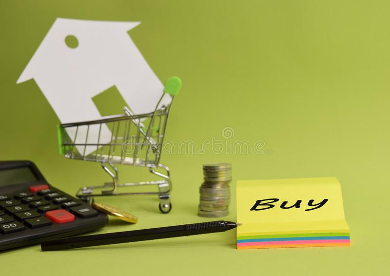 House put in a shopping cart and coin, pen, calculator on the desk. royalty free stock image