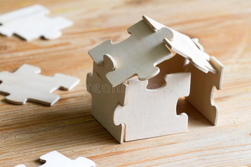 House with puzzles and planning expenses for building a house abstract concept royalty free stock photo