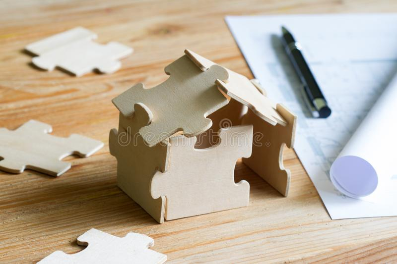 House with puzzles and planning expenses for building a house abstract concept stock photo