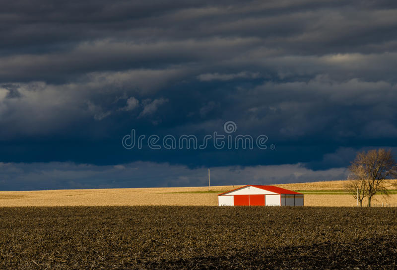 The barn with red roof under storm clouds. The barn with red roof is in the middle of nowhere under the storm clouds. The light from sun divide the field into royalty free stock image