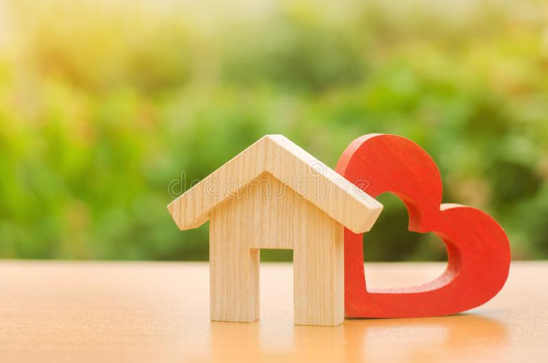 House with a red wooden heart. House of lovers. Parental hospitable home. Housing construction of your dreams. Buying and renting. Real estate. Affordable royalty free stock image