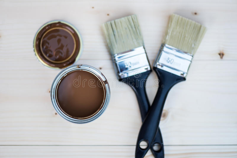 House Renovation, Brown Paint Can and Brush. Es on Wooden background royalty free stock photo