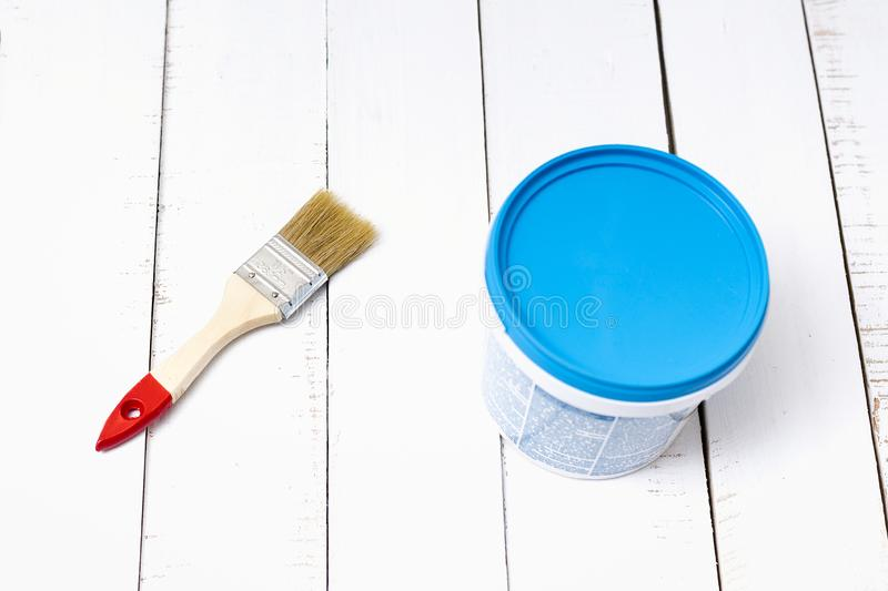 House renovation concept. Brush and a paint bucket on a background of white, shabby wooden planks.  stock images