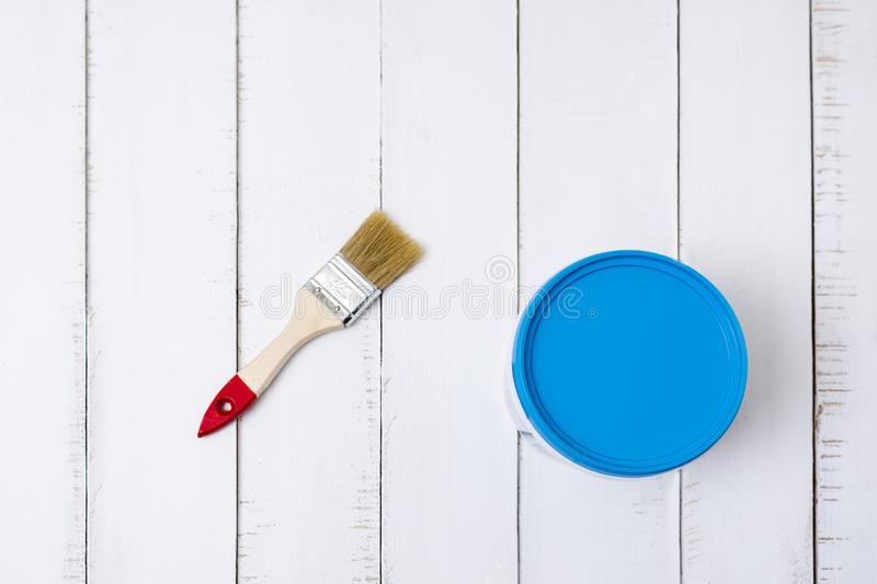 House renovation concept. Brush and a paint bucket on a background of white, shabby wooden planks. Directly above.  stock photos