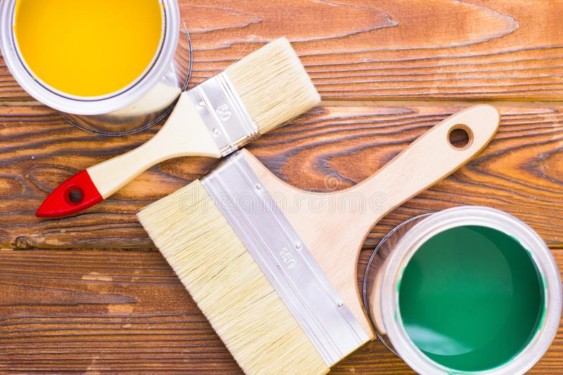 House renovation concept, colorfull paint cans and paintbrushes on dark wooden background stock photography
