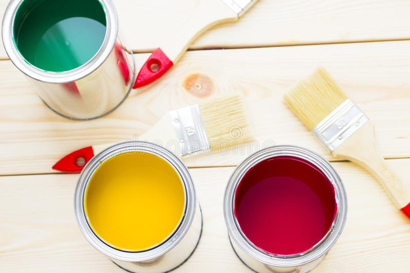 House renovation concept, colorfull paint cans and paintbrushes on wooden background royalty free stock photos