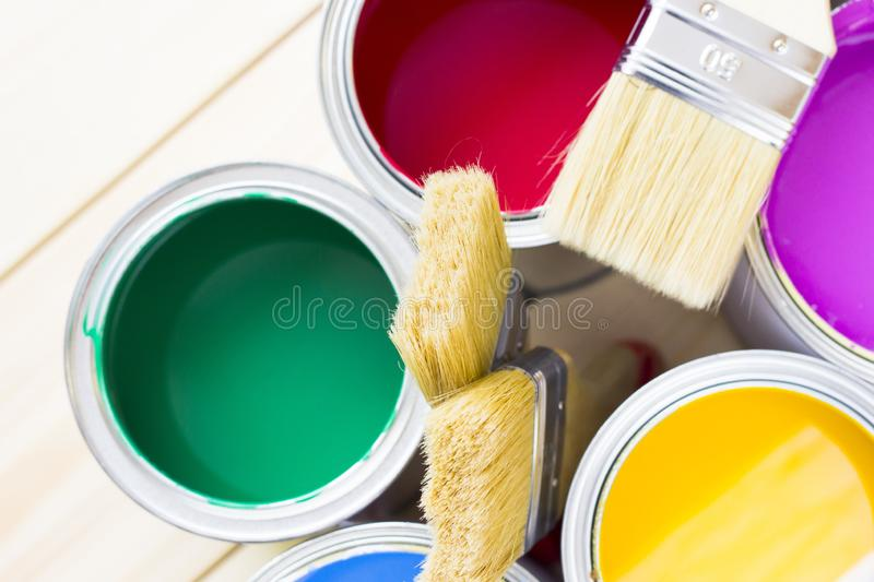House renovation concept, colorfull paint cans and paintbrushes on wooden background royalty free stock image