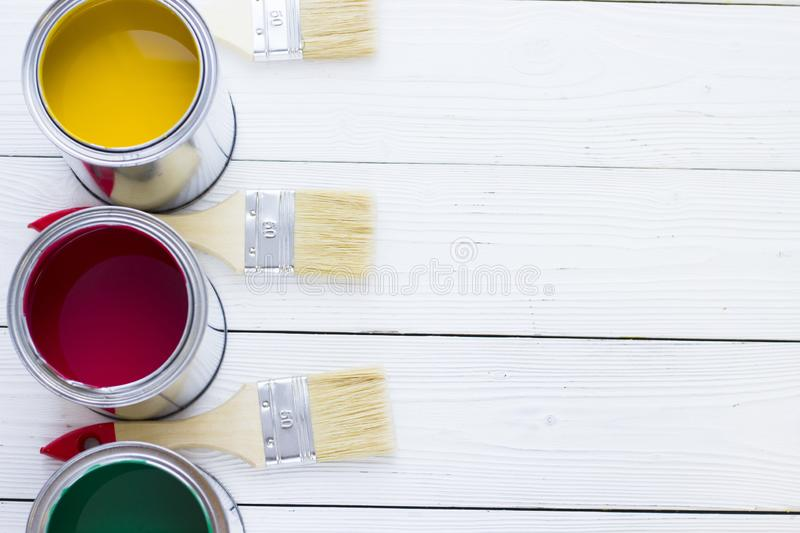 House renovation concept, colorfull paint cans and paintbrushes on wooden background stock images