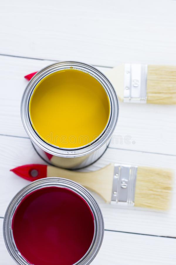 House renovation concept, colorfull paint cans and paintbrushes on wooden background royalty free stock photography