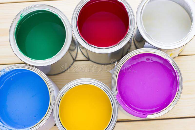 House renovation concept, colorfull paint cans on wooden background royalty free stock photos