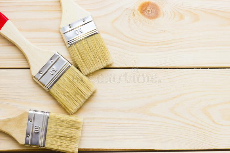 House renovation concept, colorfull paintbrushes on wooden background royalty free stock photos