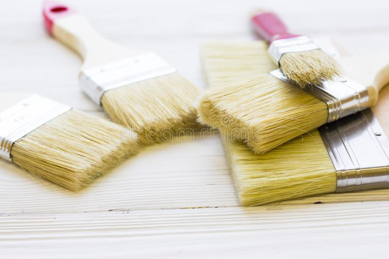 House renovation concept, colorfull paintbrushes on wooden background stock images