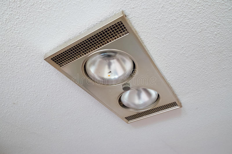 House Renovation and Remodel. Bathroom moisture exhaust fan in the ceiling with two lights at a house remodel royalty free stock image