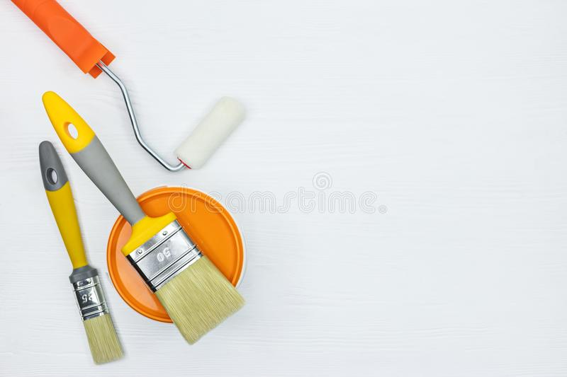 House renovation tools - brushes, paint, rollers on white wooden. Desk. view from above stock photo